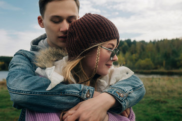 Boyfriend embracing girlfriend while standing against cloudy sky in forest
