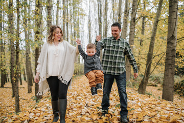 Playful parents swinging son while holding his hands in forest during autumn