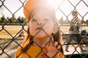 Close-up portrait of cute girl wearing cap standing against sky seen through chainlink fence during sunny day