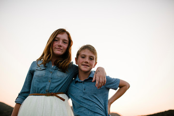 Low angle portrait of siblings standing against clear sky during sunset