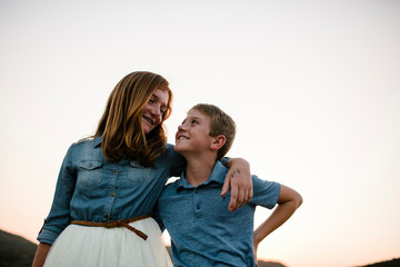 Low angle view of smiling siblings looking each other face to face while standing against clear sky during sunset