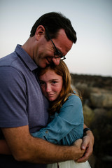 Portrait of daughter embracing father while standing on field during sunset