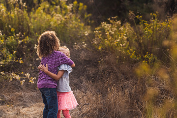 Side view of happy sisters embracing while standing on field against plants in park