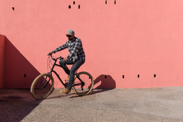 Young man riding bicycle on sidewalk