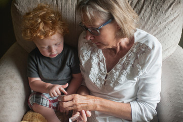 High angle view of grandmother and grandson looking at glass slab on armchair at home