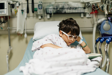 Boy wearing eyeglasses reading book while relaxing on bed in hospital