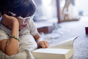 Close-up of boy reading book while lying on carpet at home
