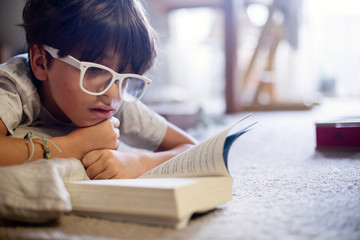 Close-up of boy wearing eyeglasses reading book while lying on carpet at home