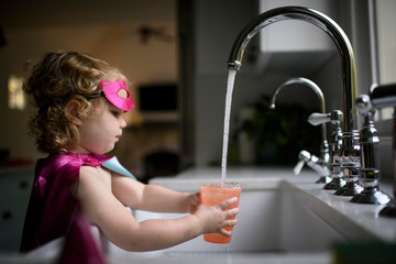 Girl filling water in drinking glass at home