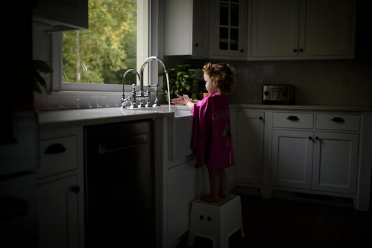 Girl washing hands in kitchen sink at home