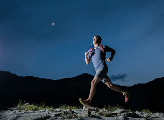 Low angle view of confident male hiker running on mountain against blue sky at night