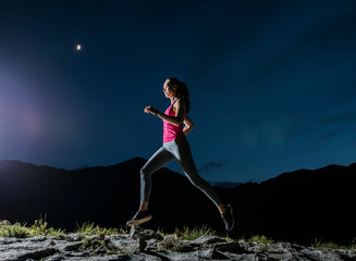Low angle view of confident female hiker running on rocks against blue sky at night