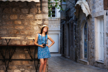 Thoughtful woman with camera looking away while standing against old building in city