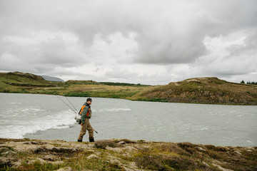 Side view of man with fishing rods walking at lakeshore against cloudy sky at Iceland