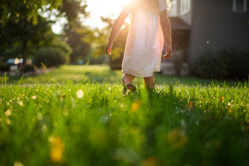 Low section of girl standing on grassy field in yard during sunrise