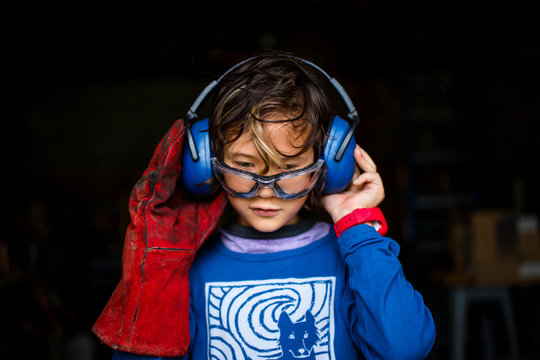 Boy wearing safety glasses standing in workshop