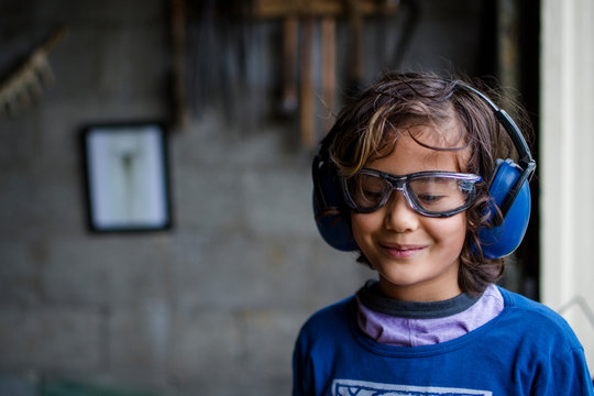 Smiling boy wearing earmuff and safety glasses standing in blacksmith workshop