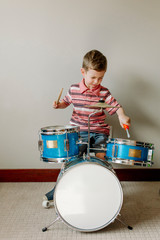 Cute boy playing drums while sitting against wall at home