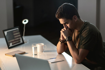 Young American soldier contemplating while writing a letter at office desk.