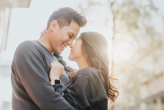 Asian couple in love embracing outdoor