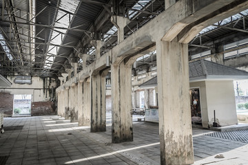 The ruins of an old abandoned factory. Perspective of abandoned warehouse from the inside with translucent roof and concrete structure.