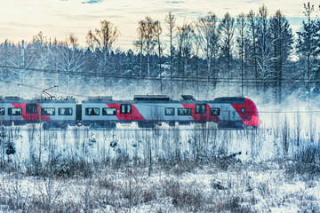 Modern high-speed train approaches to the station at winter morning time.