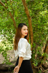 Women white skin lovely brown hair red lip wear white shirt women standing poses photography portrait In the garden has a tree as a background.