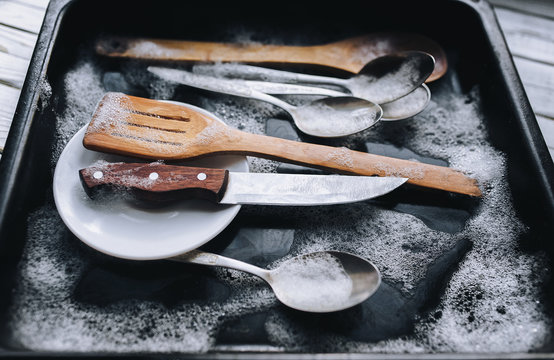 Washing dishes concept. A plate, a knife, wooden kitchen spatulas and silver spoons in the detergent foam on a black oven-tray.