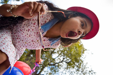 Young girl and very fashionista with floral dress and pink hat is surprised to see something incredible. In his hands he wears sunglasses and balloons.
