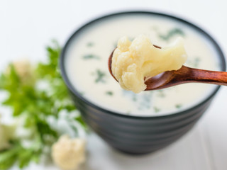 An inflorescence of cauliflower in a brown wooden spoon over a bowl of cream soup.