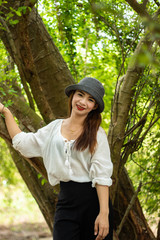 Women white skin lovely brown hair wearing a gray hat red lip wear white shirt wearing black pants women standing poses photography portrait under the tree In the garden.