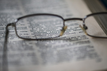 "Points are on the page of the English-Russian dictionary. The word ""presbyopia""can be seen through the glasses lens. Concept: glasses help with vision problems. Selective focus. Blurred image."