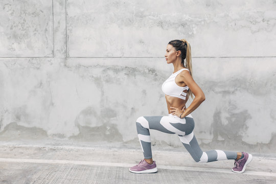 Fitness sport woman in fashion sportswear doing workout over gray wall