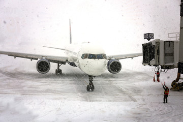 Commercial Jet Airplane Pulling up to Gate in Blizzard Snowstorm
