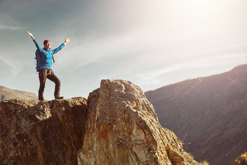 Hiker woman with backpack standing on top of a mountain with raised hands