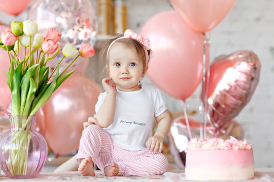 Baby girl  in the kitchen.  Celebration. Beautiful little girl celebrating birthday party with balloons and birthday cake.  One year party. Cute infant with group of  pink balls and tilips.