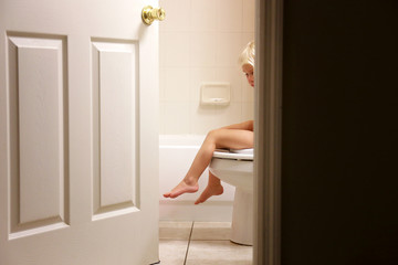Legs of Little Toddler Child Dangling over Toilet while Potty Training in Bathroom