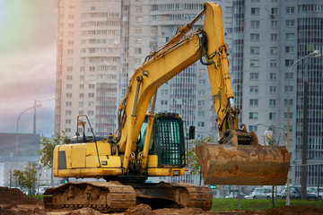 Yellow heavy duty digger on background of residential complex. Large excavator bucket collect and pours soil, stones in a quarry at construction site of road facilities and houses. Under construction