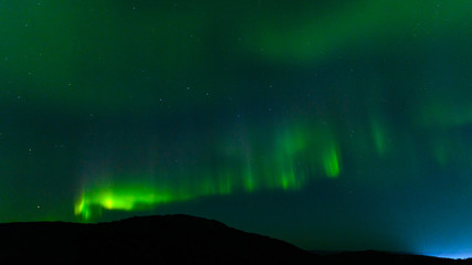 Northern lights at night over the hills.Aurora in the fall.