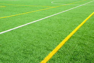 Football field green background with white and yellow lines. Sport texture.