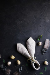 Easter holiday background with eggs. Top view of quail eggs, feather and bunny ears linen  napkin on dark rusty background. Copyspace for text
