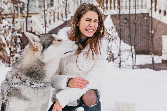 Magnificent girl in white coat enjoying winter walk with her funny dog. Outdoor portrait of lovely european woman playing with husky at snowy yard.