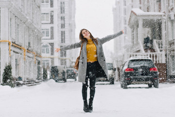 Full-length portrait of romantic european lady wears long coat in snowy day. Outdoor photo of inspired brunette woman enjoying free time in winter city.