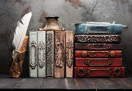 Vintage books on a wooden shelf,  paper scroll with a wax seal,.iinkwell and feather for writing. Retro still life