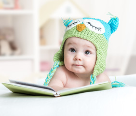 baby infany in funny owl knitted hat owl lying with book in nursery