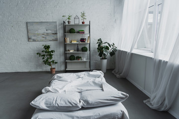 modern interior design of bedroom with rack, plants, bed, brick wall and copy space