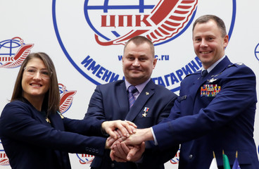 ISS crew members Aleksey Ovchinin of Russia and Nick Hague of the U.S., along with Christina Koch of the U.S. pose for a photograph during a news conference in the Star City near Moscow
