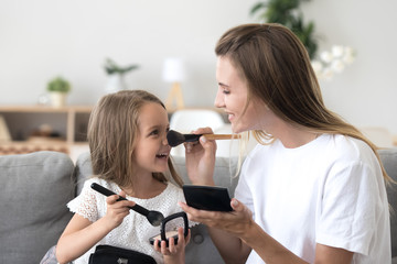 Happy mother and little daughter playing, doing makeup together