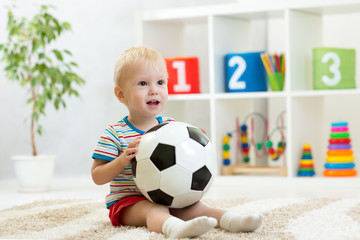 Pretty baby boy plays with ball in nursery