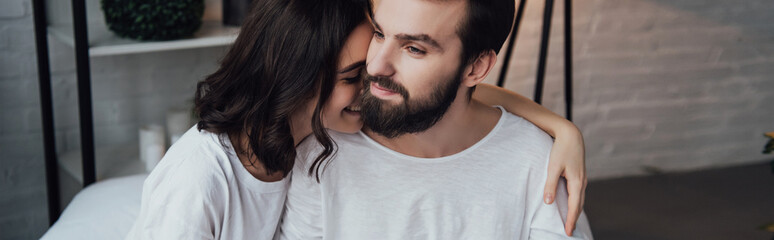 beautiful smiling woman hugging handsome bearded man at home